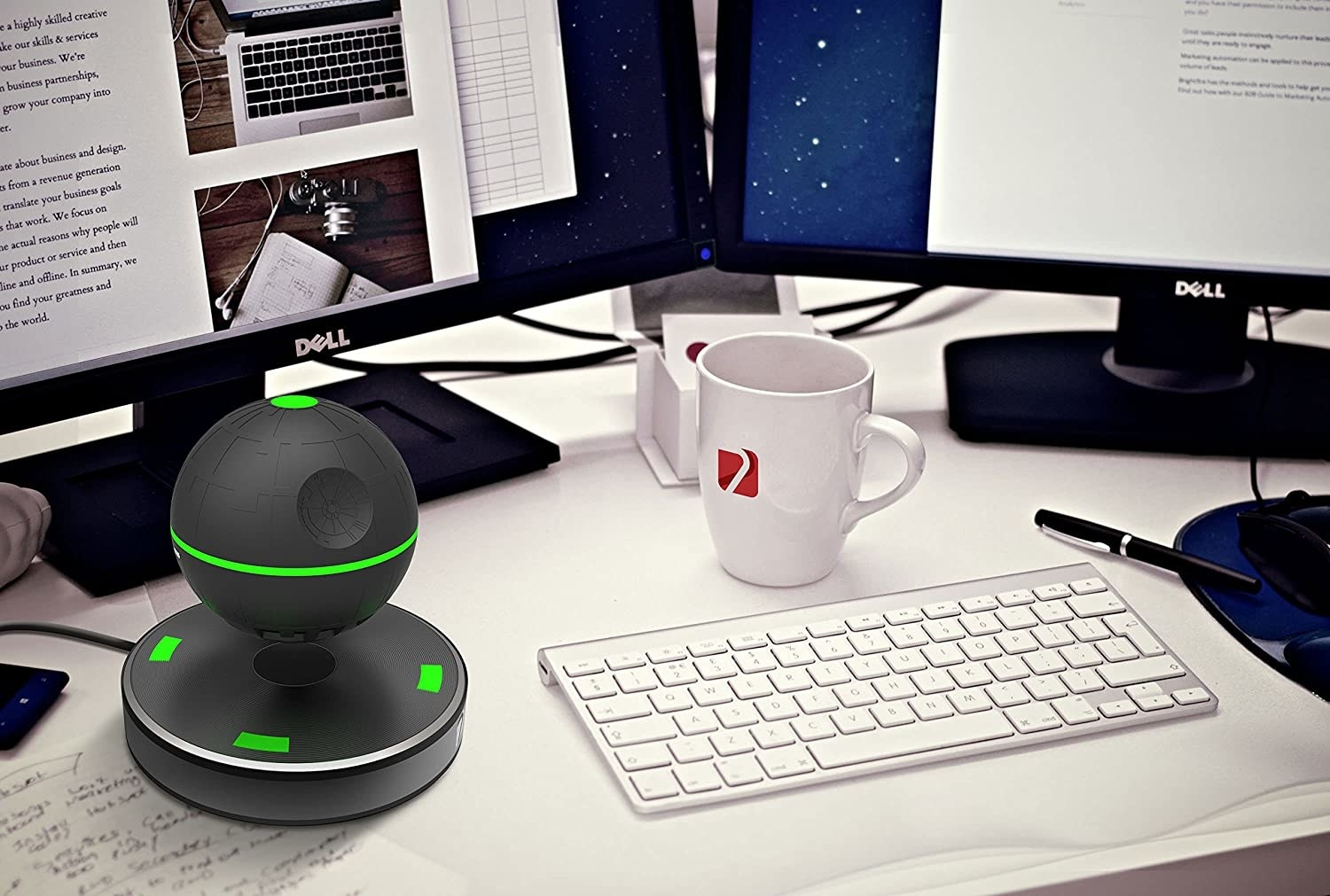 Green and black floating speaker on a desk with a keyboard and monitor