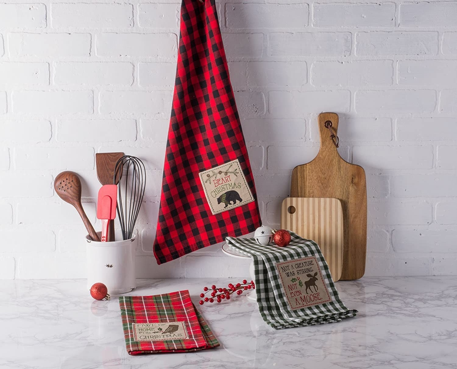 A trio of holiday-themed gingham kitchen linens on a marble countertop