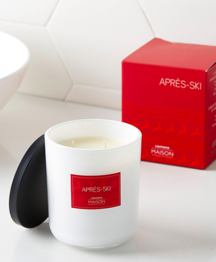 A close up of a candle on a simple surface, with a label that says Apres Ski