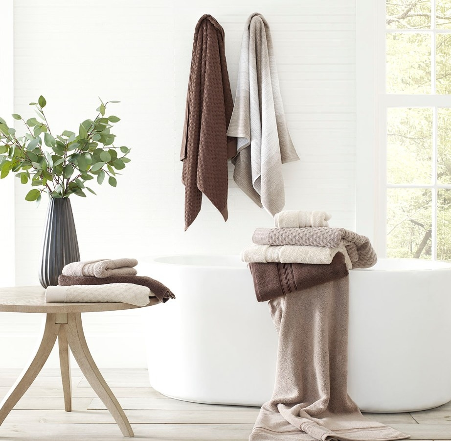 Brown, white and beige bath towels draped over white bath tub, hanging on hook, and folded on table