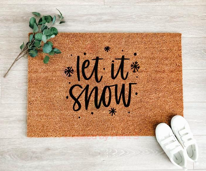 A coarse door mat that says let it snow
