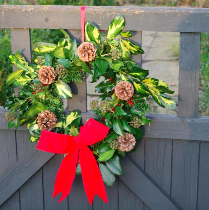 A handmade wreath hung on a wooden gate