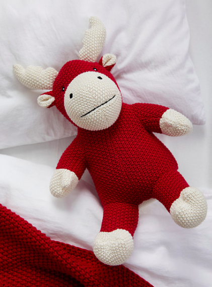 A knitted moose tucked into matching bed sheets
