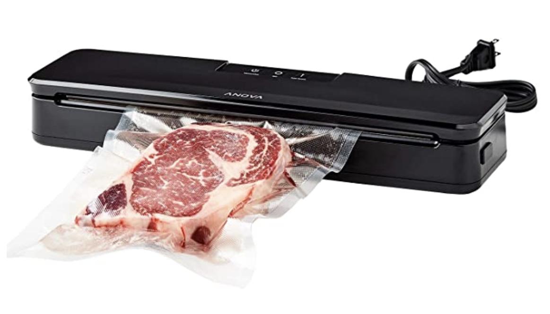 A black rectangular vacuum sealer sealing plastic around a piece of steak meat