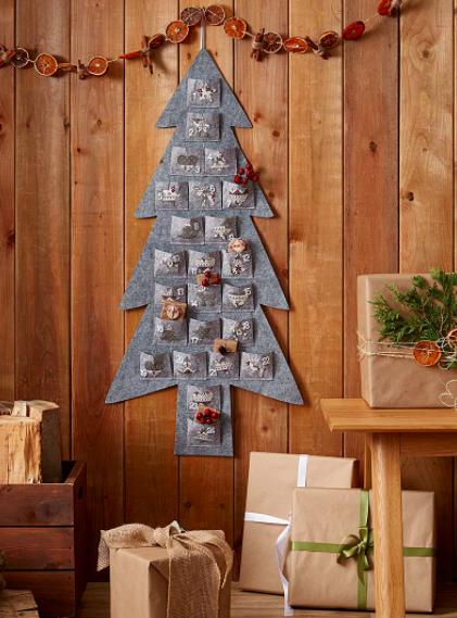 A felt pine tree with pockets hung on a wall