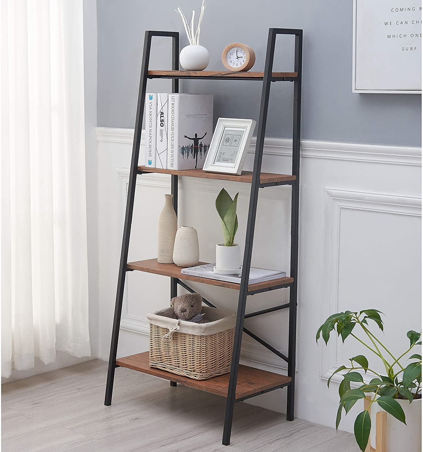 Black and wood ladder shelf with books, trinkets, and storage baskets
