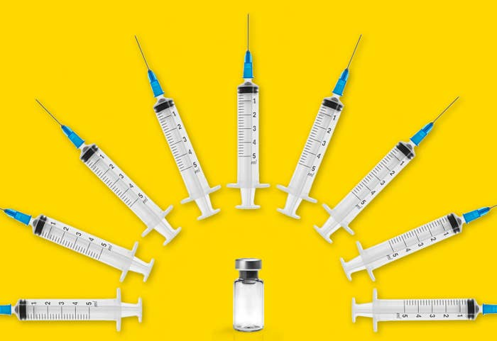 Several syringes arc over a vaccine vial.