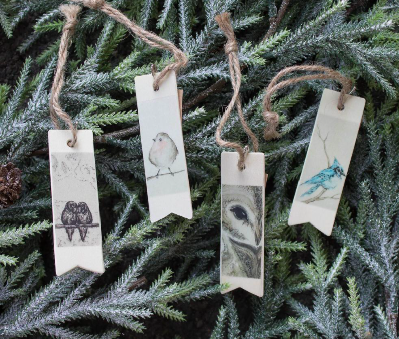 A series of wildlife-themed wooden gift tags on pine boughs