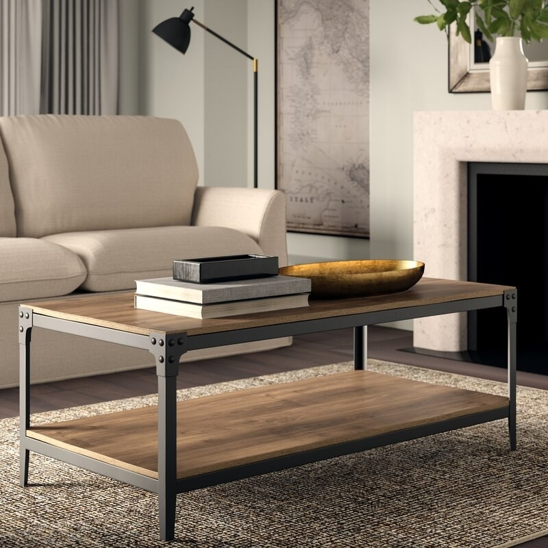 Metal and wood rectangular coffee table with books on top