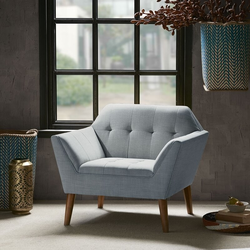 angular light blue armchair with wooden legs in front of a window