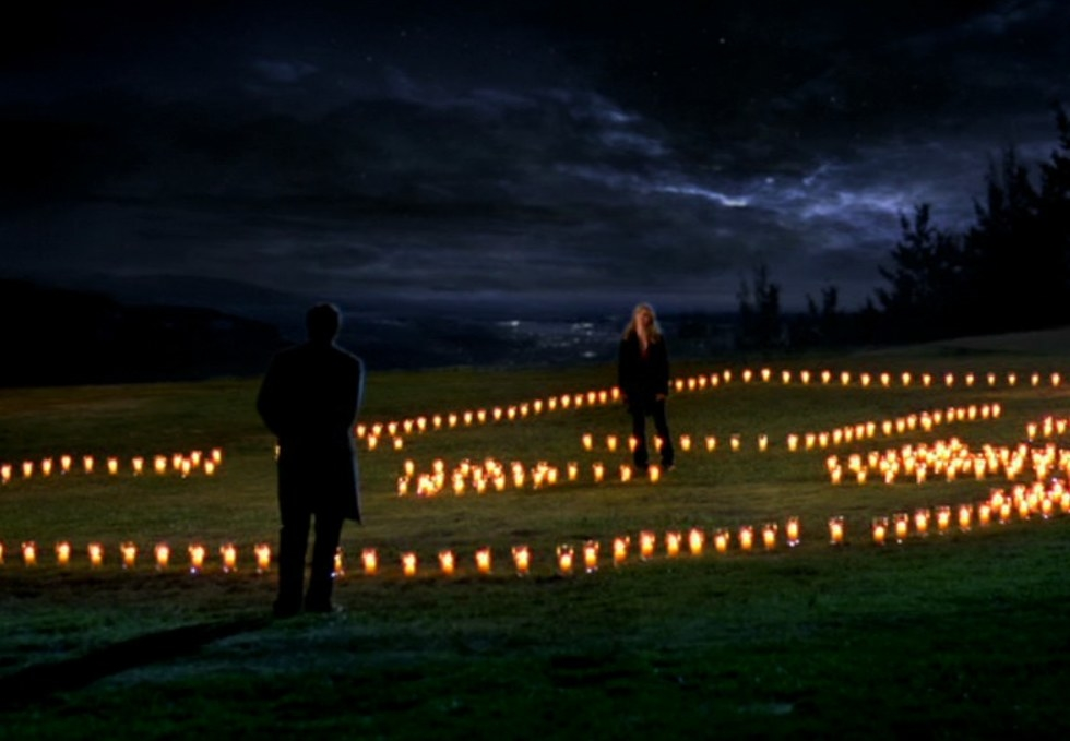 Meredith standing inside the house of candles that she built while speaking to Derek.