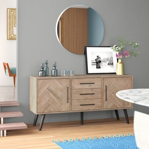 wood buffet table with splayed legs with various home decor sitting on top