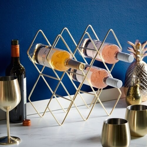 Gold, geometric wine rack holding three wine bottles and sitting on a counter