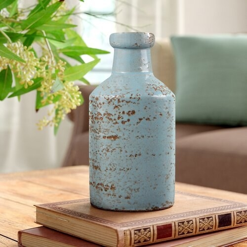 light blue milk jug base sitting atop of books on a table