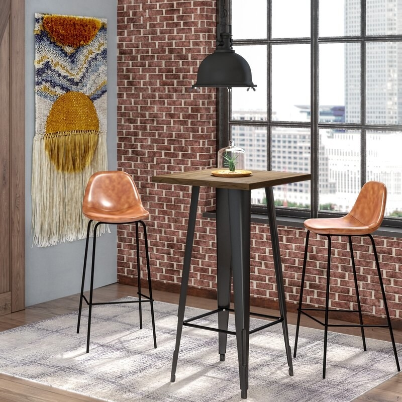 Tan faux leather bar stools with metal frame next to a high top table.