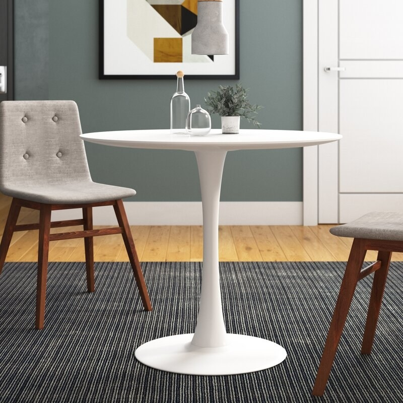 round white dining table with chairs nearby
