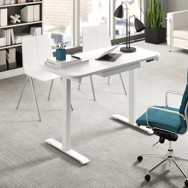 white standing desk with laptop on top and chairs nearby