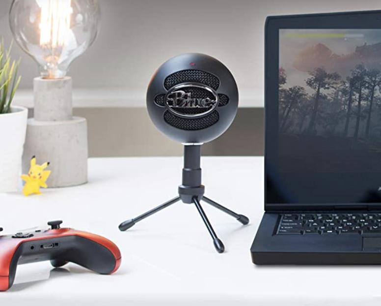 A circular speaker sitting on a small tripod on a desk