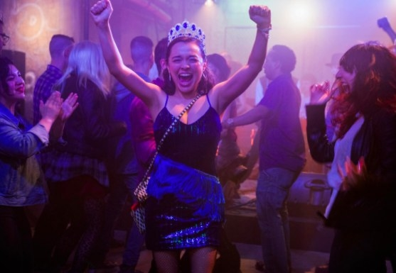 Lily wears a crown and triumphantly dance sin a crowd of people
