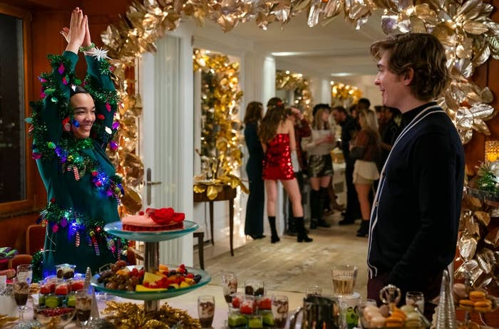 Still from Dash & LIly: Lily shows her Christmas Tree dress to Dash as they stand near a food table at a party