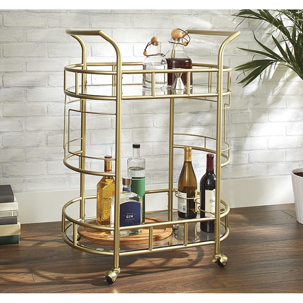 The gold bar cart in front of a brick wall
