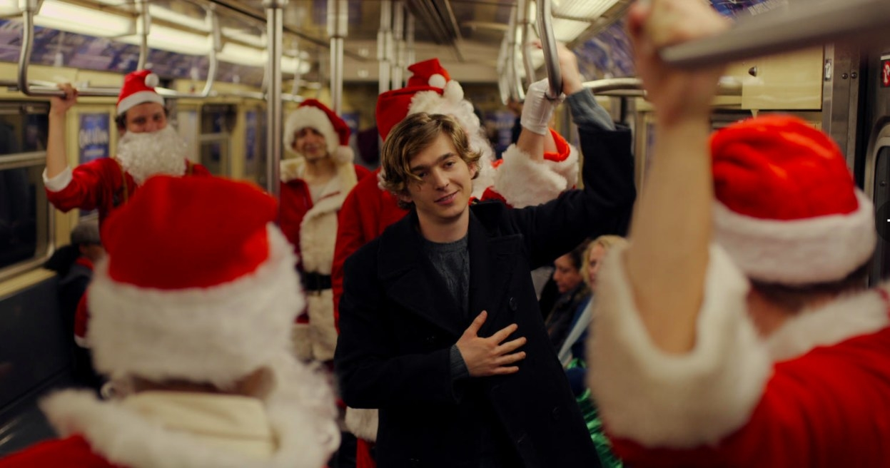 Dash stands on a subway car full of people in Santa costumes
