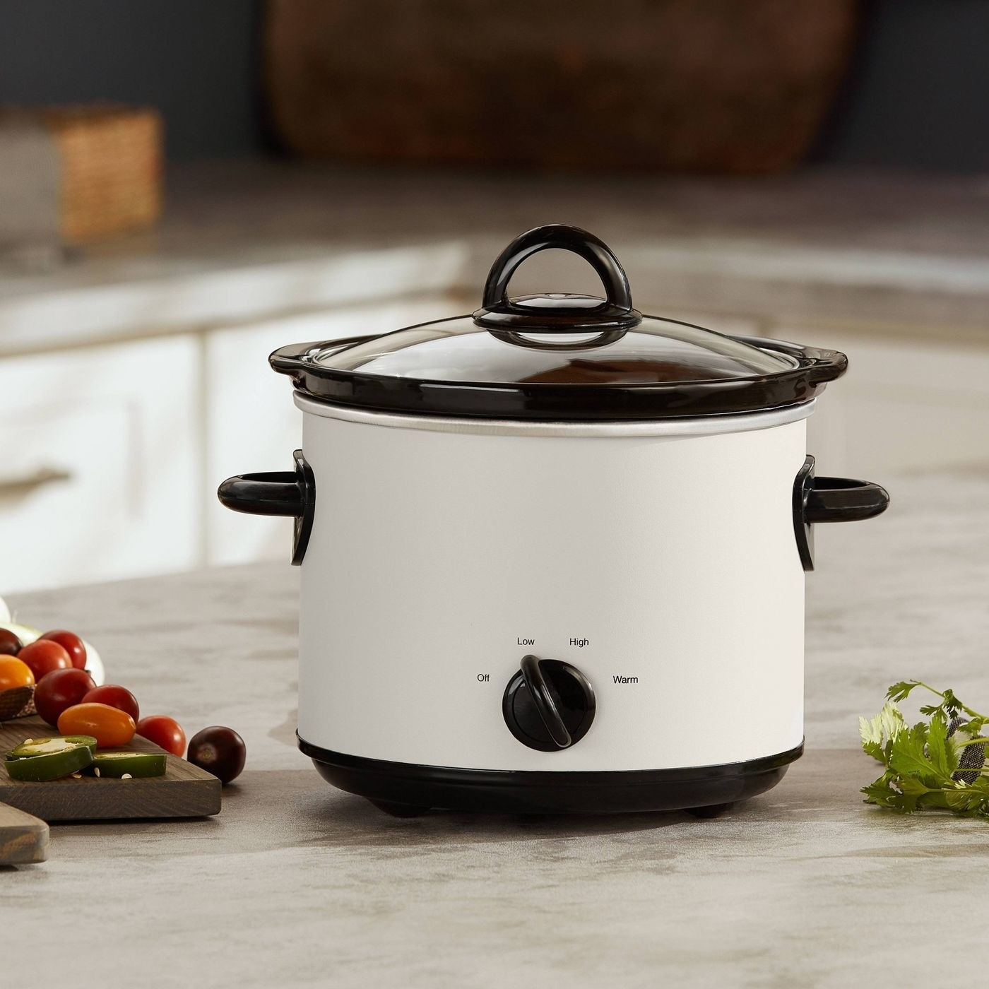 The slow cookers, which has a matter, cream body, and black handles and accents