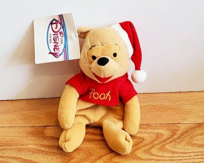 Winnie the Pooh Beanie Baby type toy wearing a Santa hat.