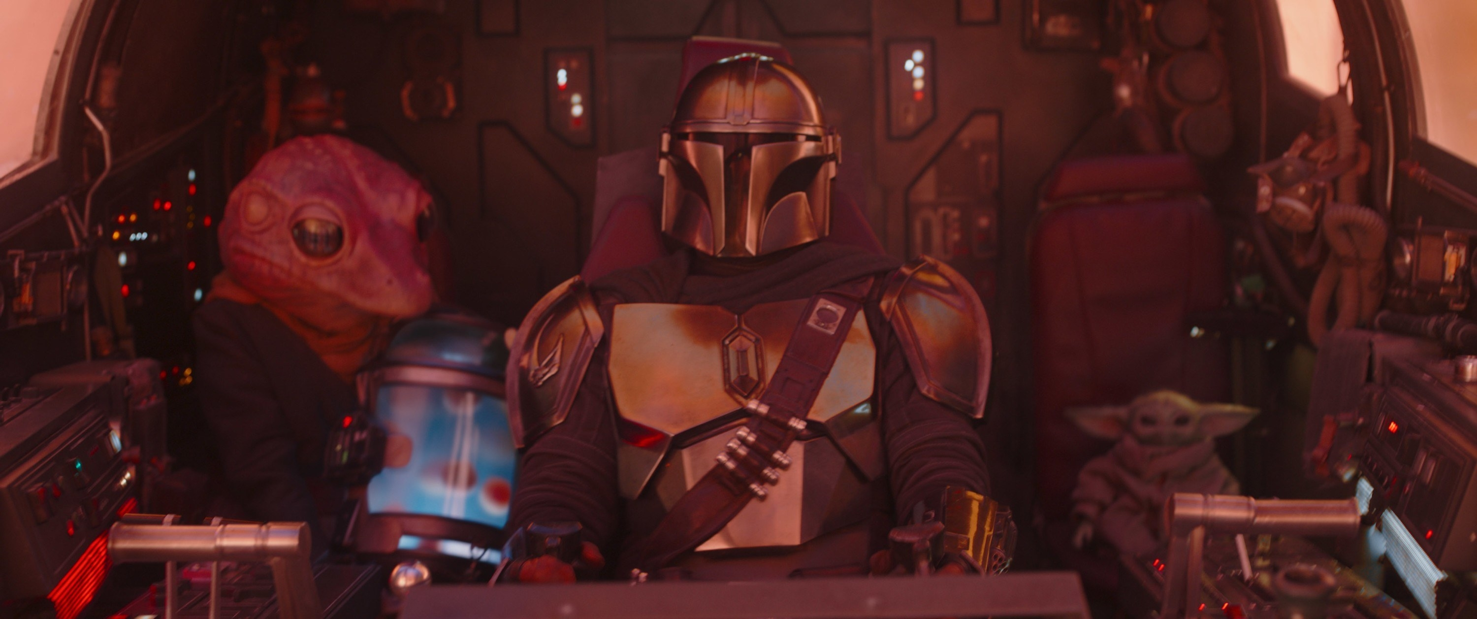 The Mandalorian pilots a spacecraft, while Baby Yoda sits behind him