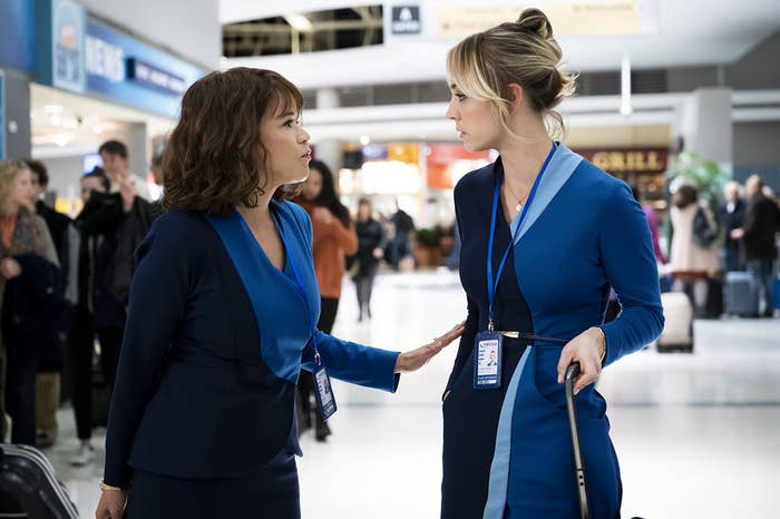 A woman in a deep and intimate conversation with another woman in the middle of an airport.