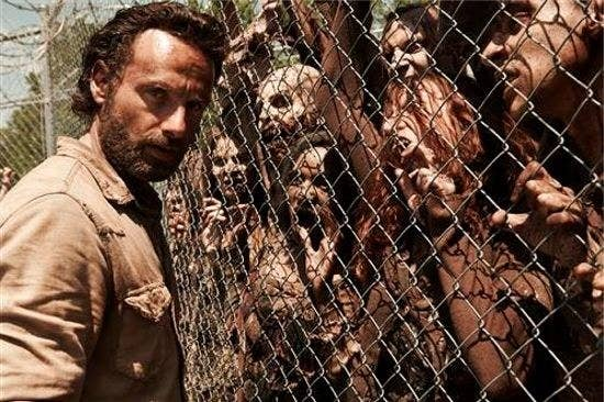 A man standing before a fence with zombies on the other side struggling to get to him.
