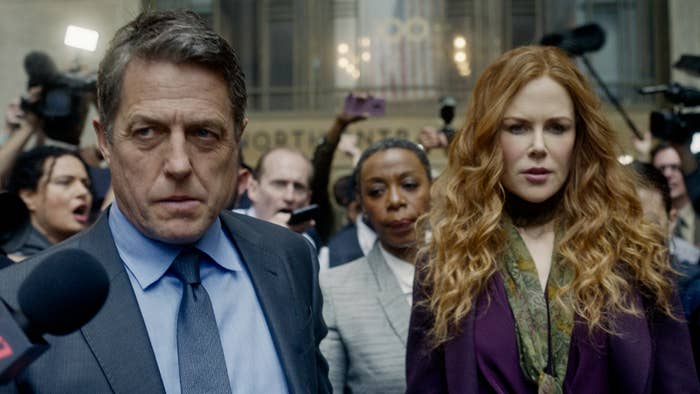 Hugh Grant and Nicole Kidman standing before a crowd of reporters looking grim.