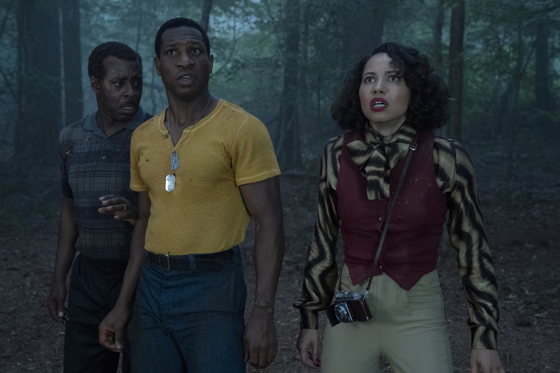 Two men and a woman looking terrified in a forrest.