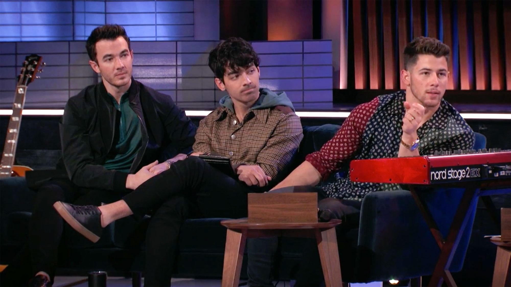 The Jonas Brothers sitting on a couch, looking like they're giving someone advice.