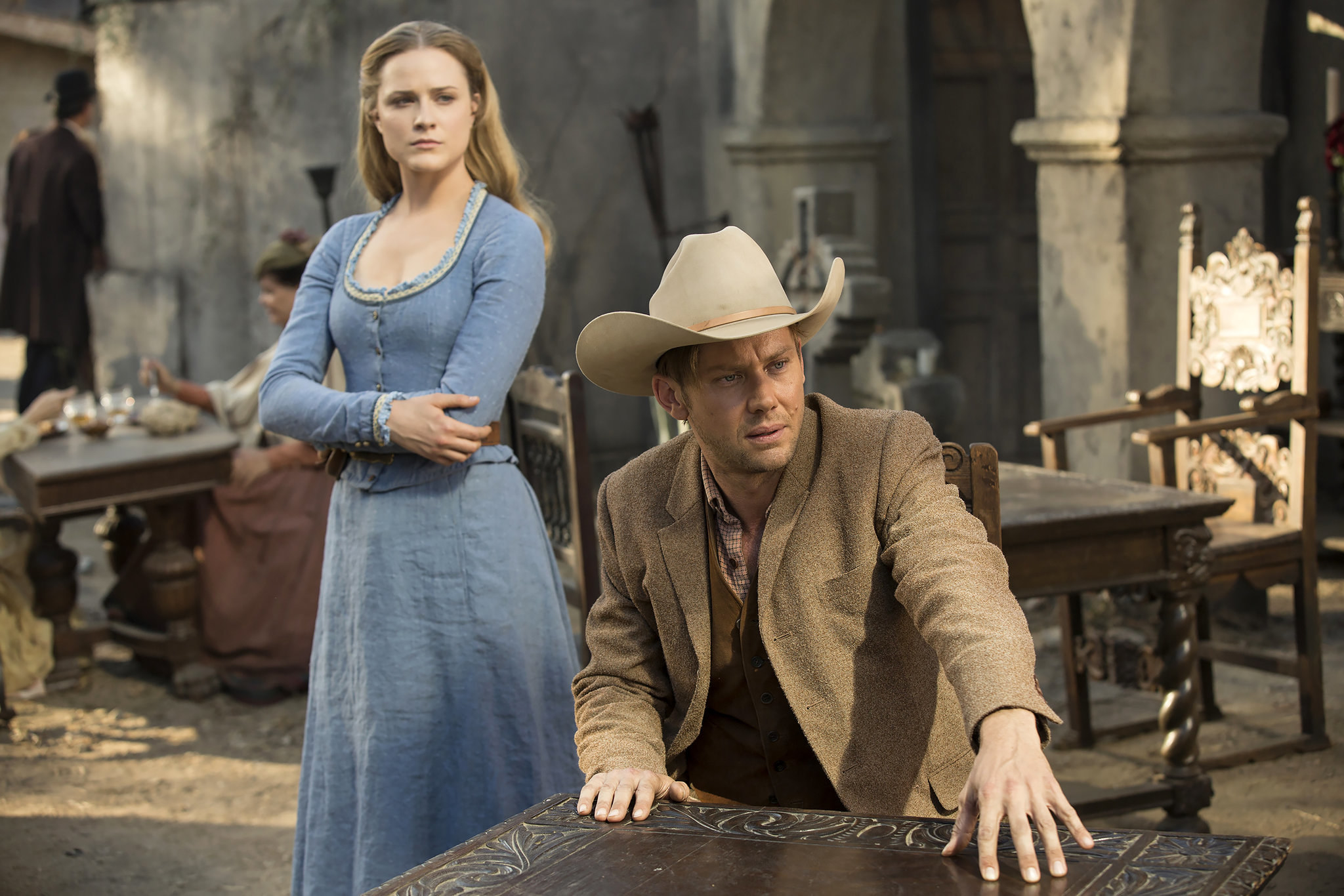 A man in a cowboy hat sitting at a table with a woman in old timey clothing standing behind him.