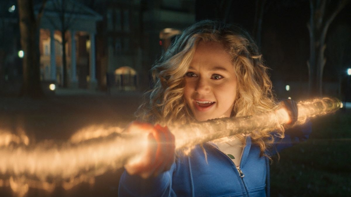 A girl looking incredibly impressed by her superpowers as she creates a rod of energy in her hands.