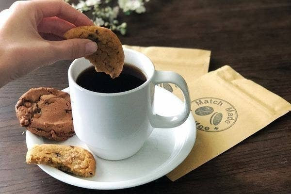 A person dipping a cookie into a cup of coffee
