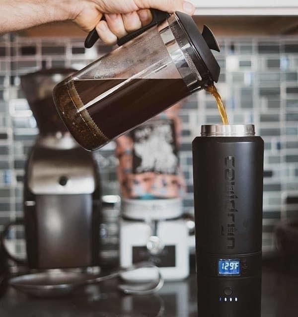 A person pouring coffee into the black mug