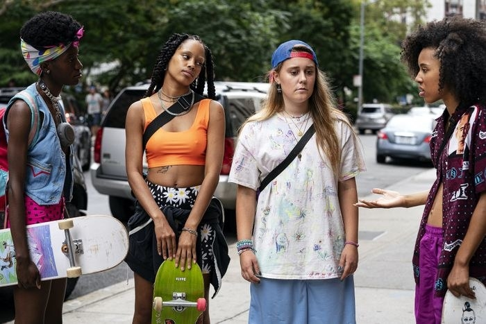 Four skaters who happen to be women standing on a street having a conversation.