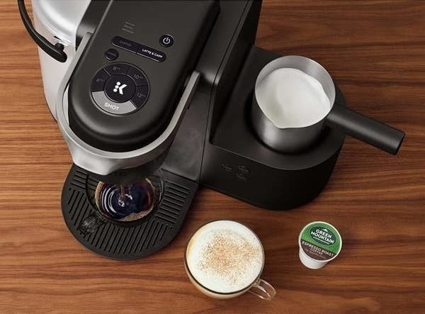 The coffee maker brewing a cup of coffee while frothing milk with a cup of cappuccino and a K-cup sitting next to it