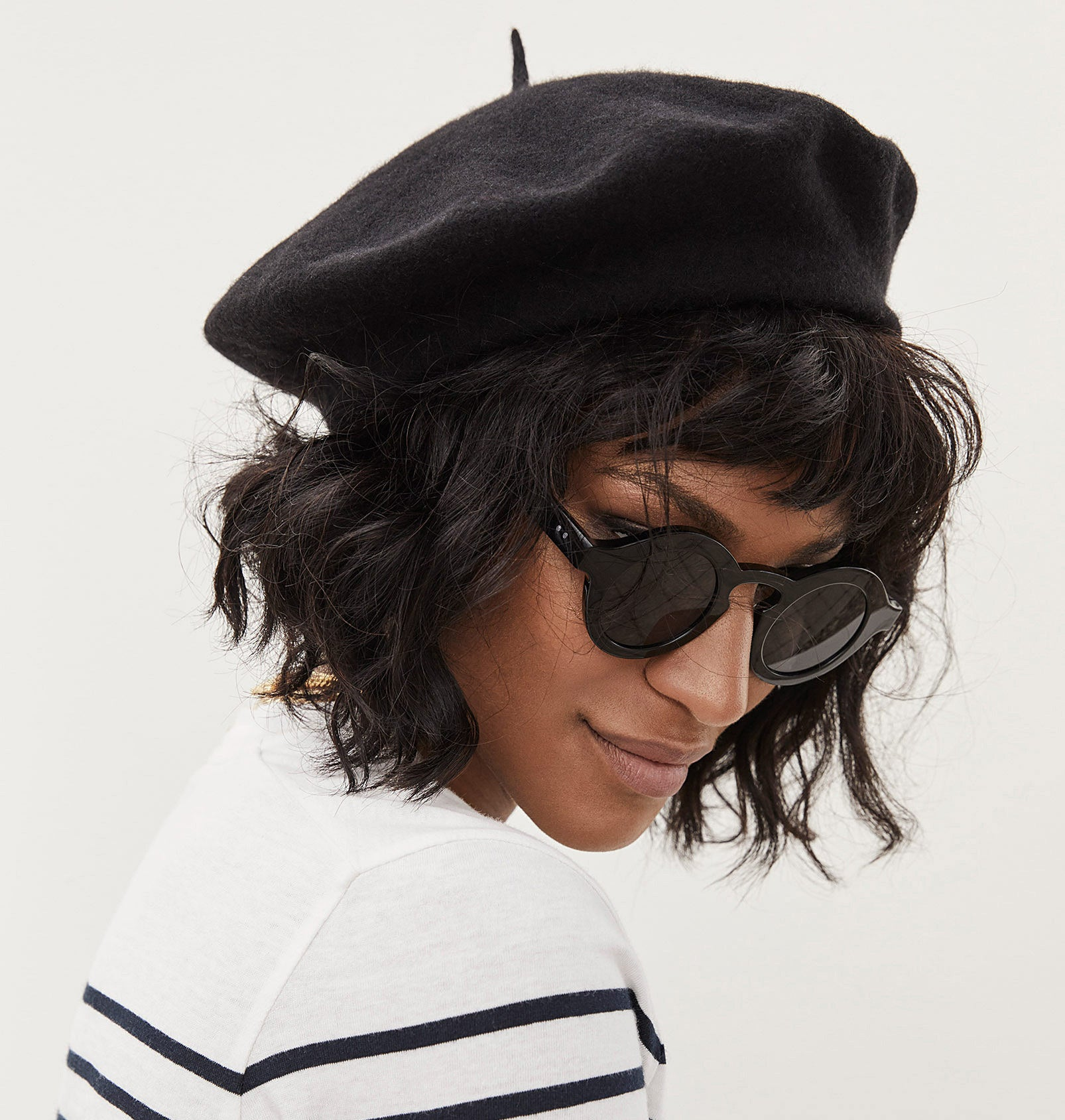 A person wearing the beret and sunglasses