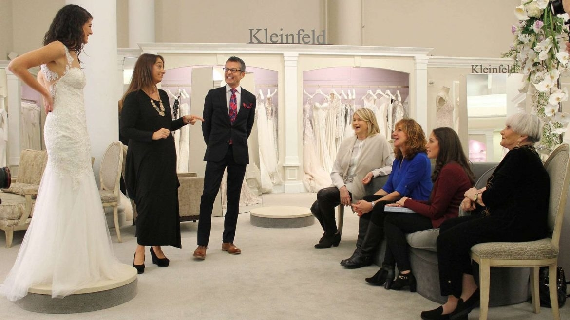 A woman trying on a wedding dress in front of family and friends in a bridal shop.