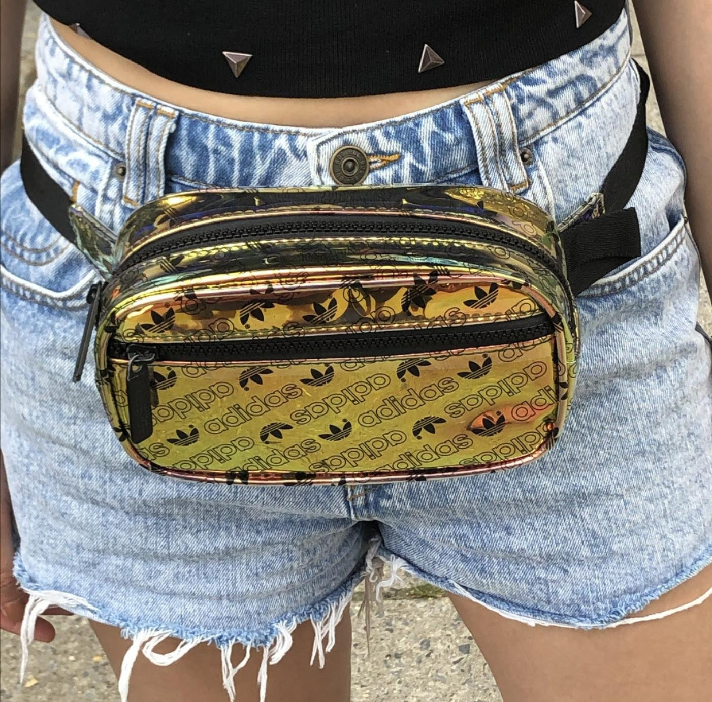 genevieve wearing a small gold iridescent waist pack covered in the adidas logo