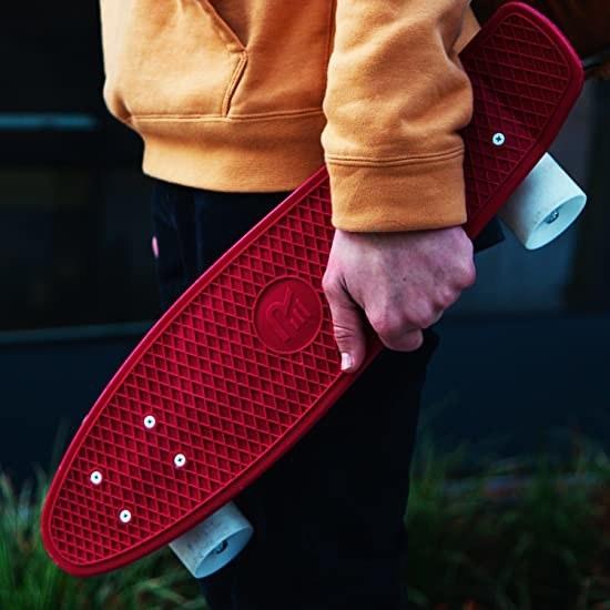 A person holding the skateboard against their leg