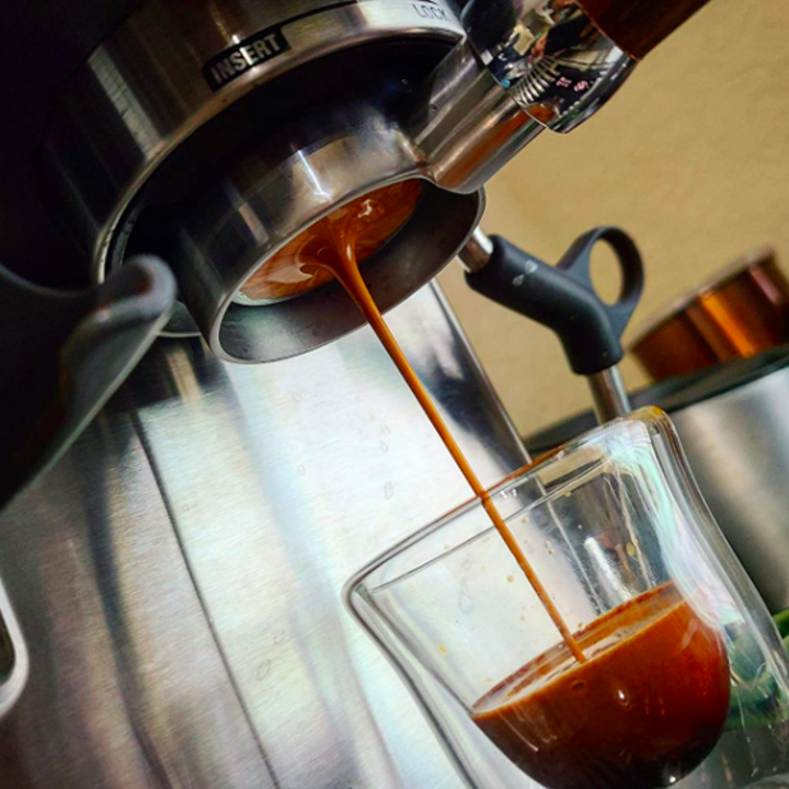 reviewer photo showing espresso machine pouring an espresso shot