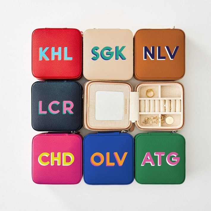 Eight of the monogrammed cases in varying colors including black, pink, blue, green, tan, and red