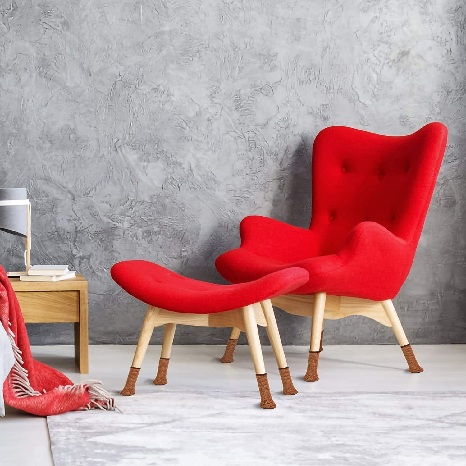 Bright red arm chair and foot rest with brown chair socks on the bottom
