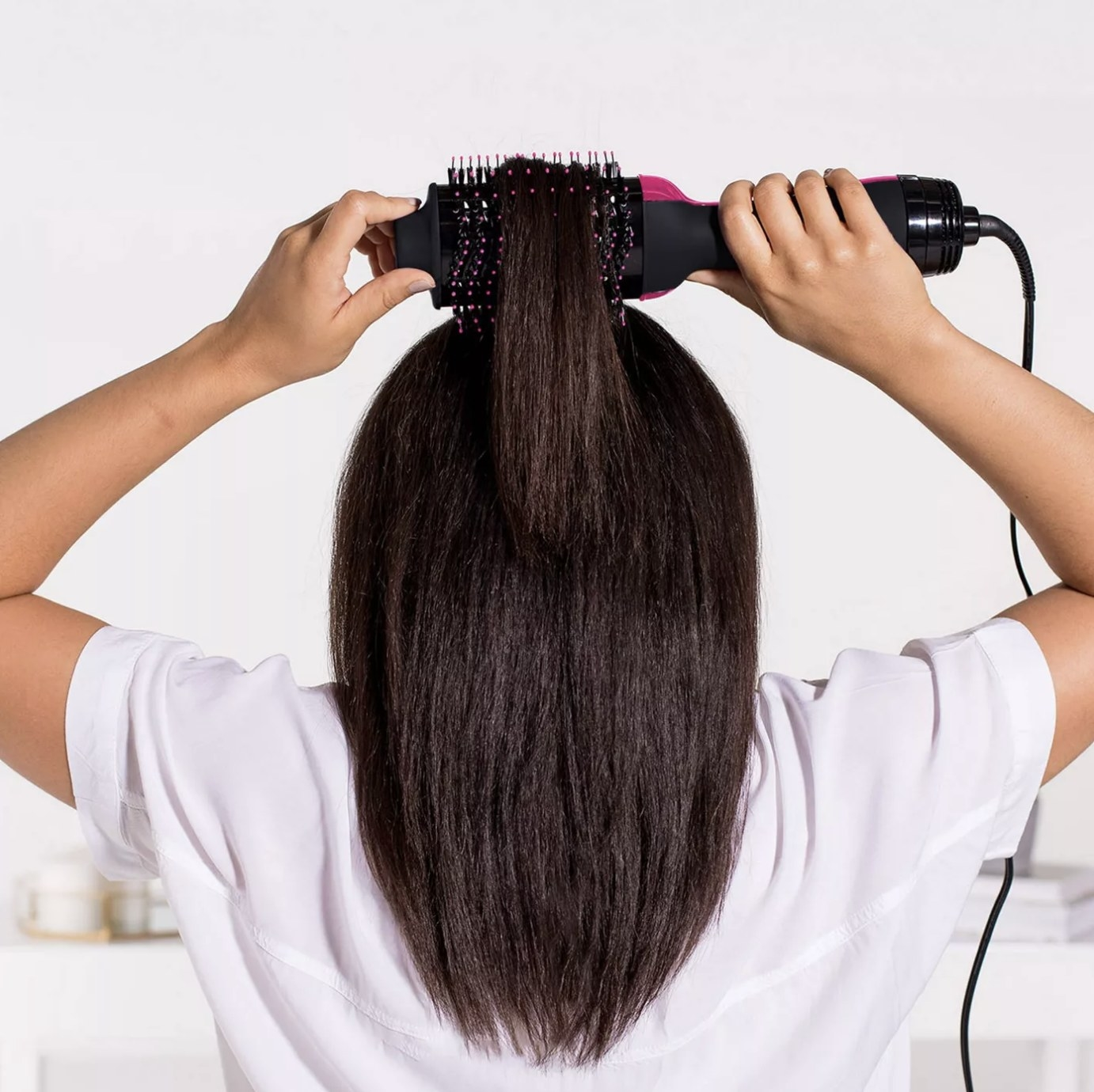 Model is blow-drying the back of her hair with the brush