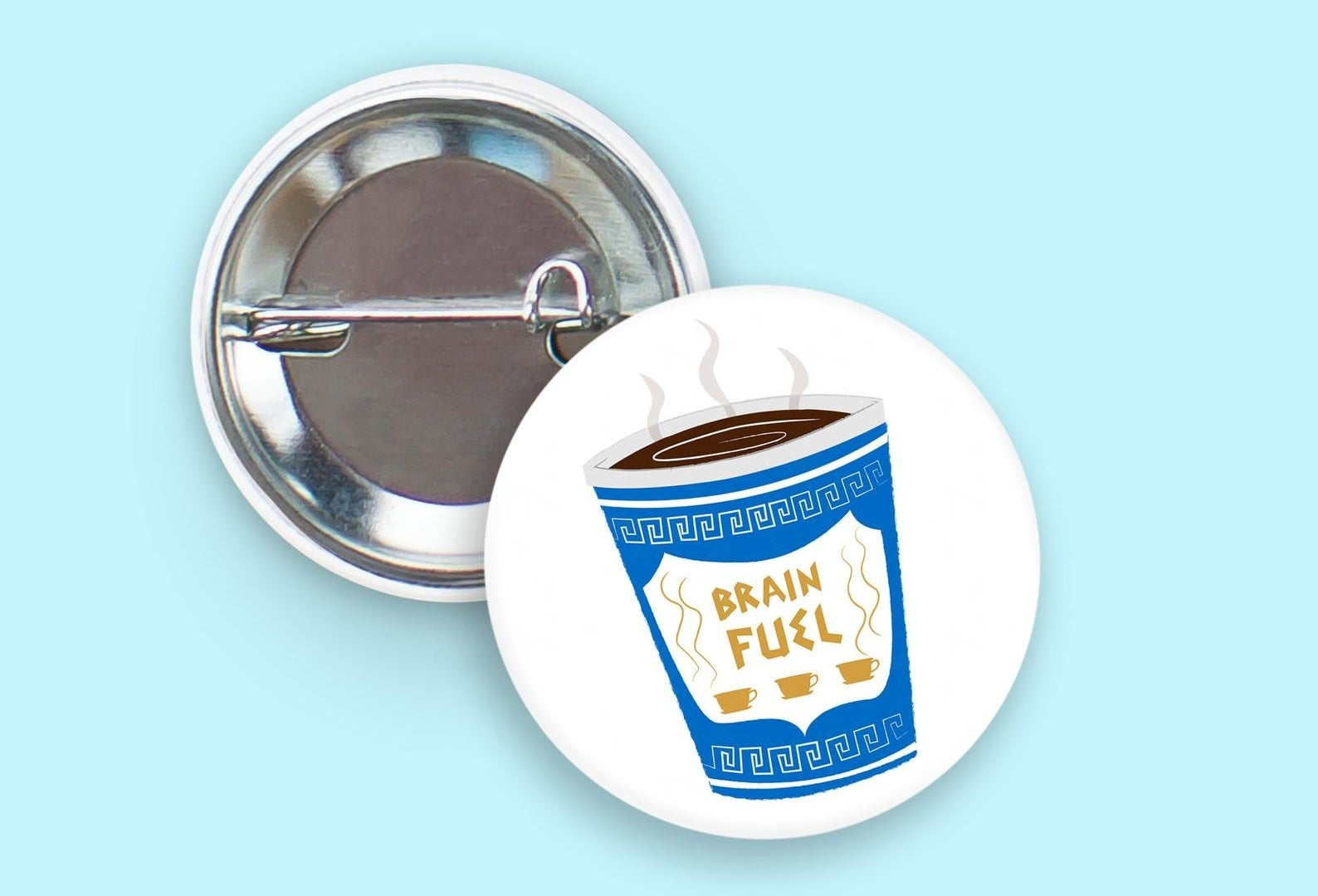 """the white pin with an illustration of a blue greek coffee cup that reads """"brain fuel"""""""