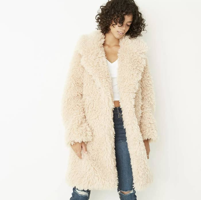 Model is wearing a cream faux fur coat, white tee, and denim jeans